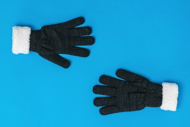 Black and white knitted gloves reach out to each other on a blue background. the concept of hope and meeting. fashion women's accessories.