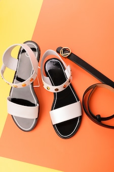 Black-white leather women's summer sandals on a yellow-orange isolated background.