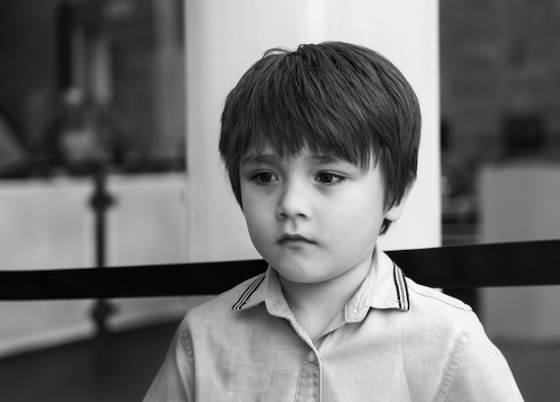 Black and white lonely kid standing alone with sad face