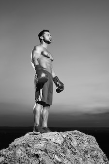 Black and white low angle shot of a handsome young strong muscular athletic man wearing boxing gloves looking away thoughtfully after training outdoors copyspace sports motivation boxer boxing.