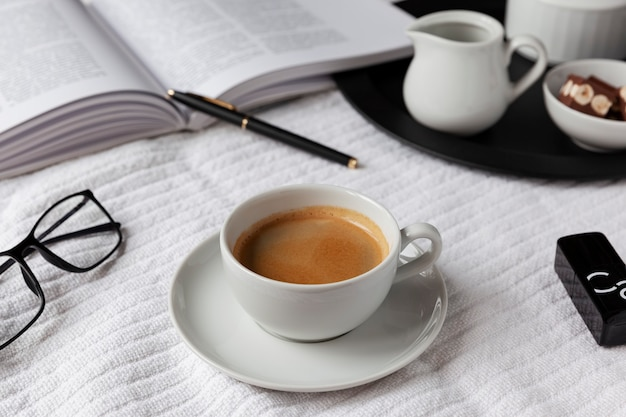 Black&white mood. cup of espresso on a white plaid with a book, glasses and pen. milk and chocolate on a black tray