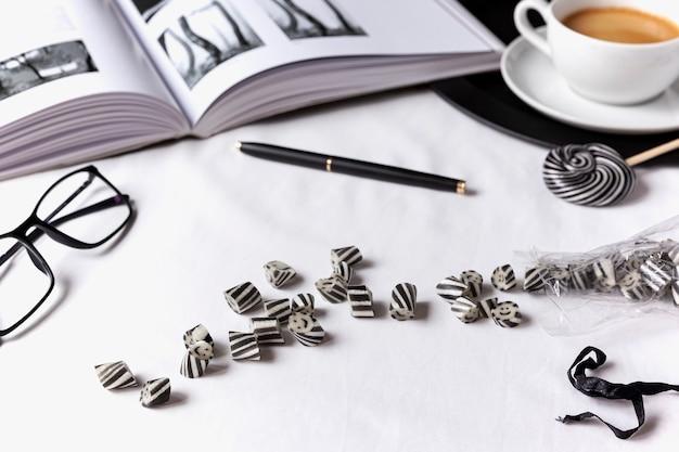 Черно-белое настроение. на белой простыне с книгой, очками и ручкой разбросаны людишки. чашка кофе на черном подносе
