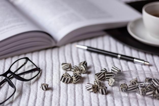 흑백 무드. 책, 안경 및 펜 흰색 격자 무늬에 흩어져있는 앤디. 검은 쟁반에 커피 한잔