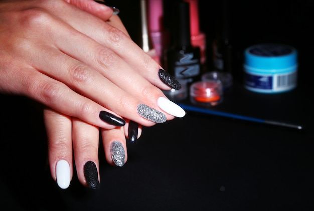 Black, white nail art manicure. holiday style bright manicure with sparkles. beauty hands. stylish nails, nail polish