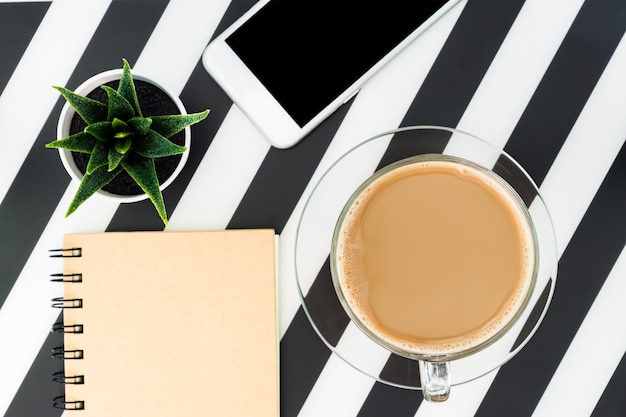 Black and white office desk table with blank notebook, smartphone, cup of coffee and supplies. top view with copy space, flat lay.