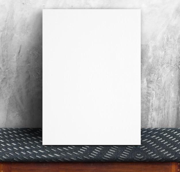 콘크리트 벽과 패브릭 테이블에 기대어 검은 백서 포스터, 템플릿 텍스트 추가를 위해 모의 프리미엄 사진