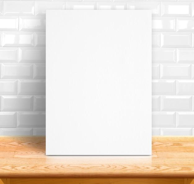 Черная белая бумажная плакатка на белом столе из керамической плитки и деревянного стола, шаблон макет для добавления текста