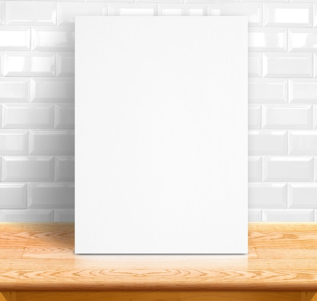 Black white paper poster lean at white ceramic tiles wall and wood table,template mock up for adding your text