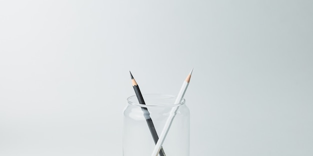 Black and white pencils in a glass jar
