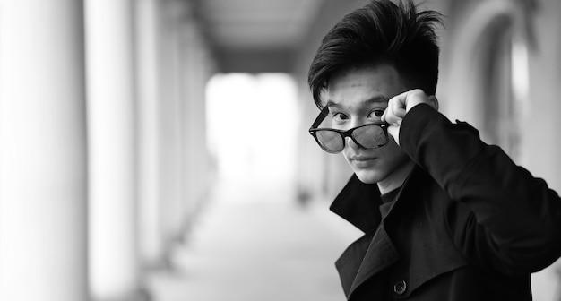 Black white photo of asian young man outdoors posing at camera