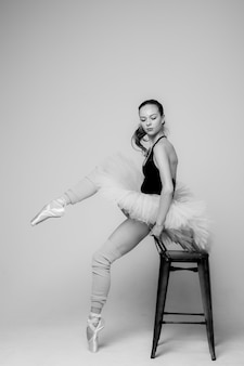 Black and white photo of a ballerina. ballerina is sitting on a chair doing stretching for legs.
