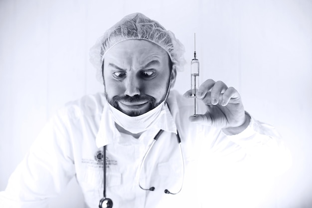Black and white photo of  bearded doctor in a white coat and an old syringe