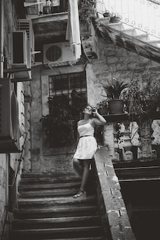 Black and white photo of beautiful woman in summer dress standing on old stone staircase