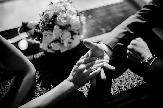Black and white photo of bride and groom holding each others hands