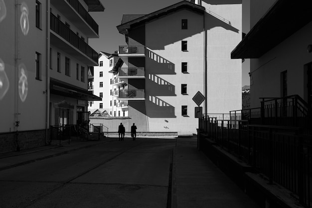 Black and white photo of city street with long shadows.