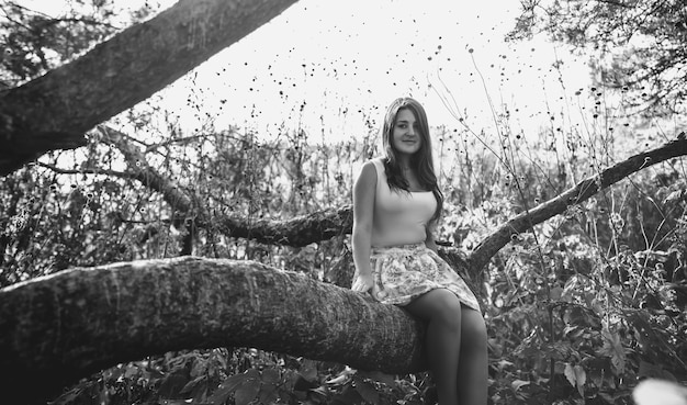 Black and white photo of cute young woman sitting on big branch at meadow