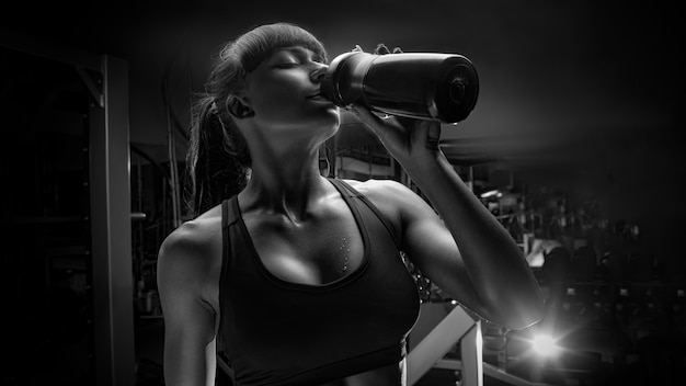 Black and white photo of fitness woman drinking water from bottle