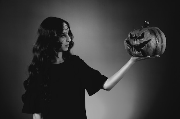 Black and white photo of girl looking at pumpkin