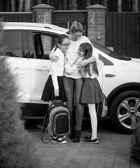 Black and white photo of happy mother hugging daughters after school