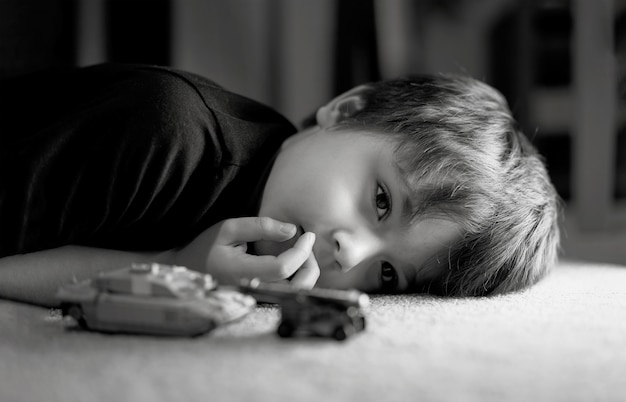 Black and white photo of lonely boy laying down on floor looking out deep in thought