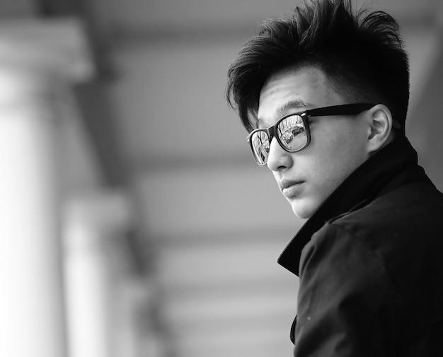 Черно-белые фото азиатского молодого человека на открытом воздухе, позирующего перед камерой