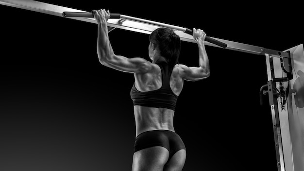 Black and white photo of professional pull up workout exercise back lats muscles