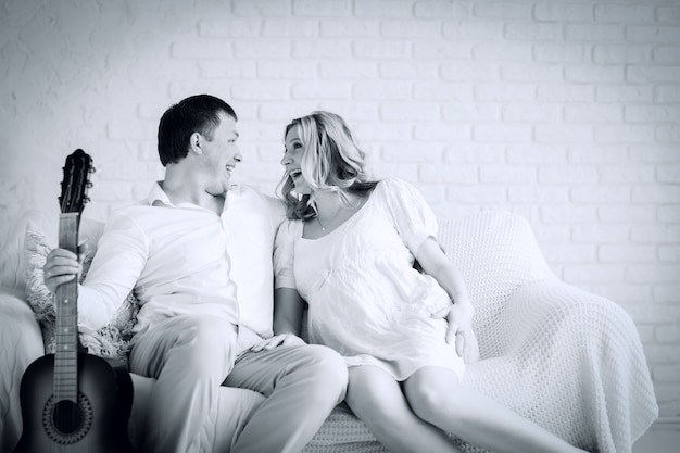 Black and white photo in retro style. cheerful husband and wife sitting on sofa in living room