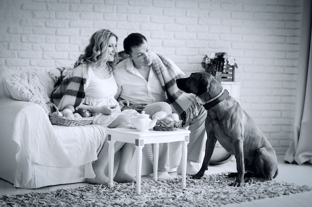 Black and white photo in retro style. happy family sitting in the living room in the morning