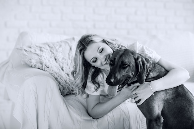 Black and white photo in retro style. portrait of a young pregnant woman with a dog