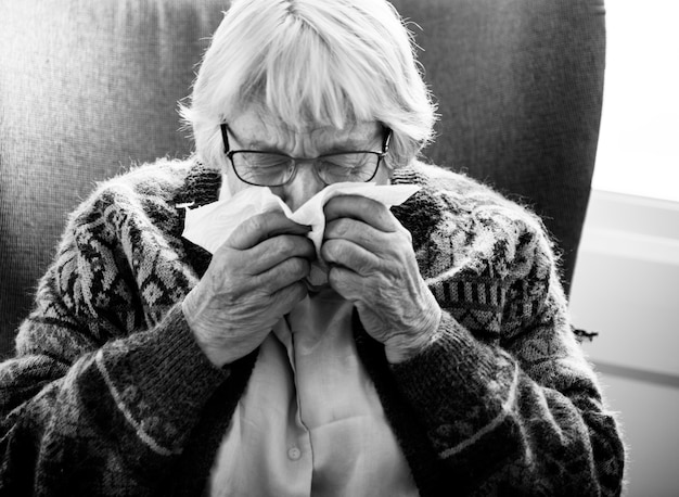 Black and white photo of senior woman sneezing