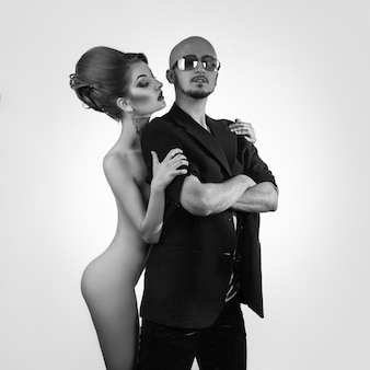 Black and white photo of serious strong man with hot naked woman