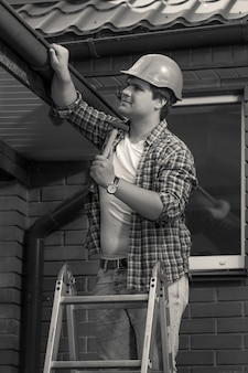 Black and white photo of worker repairing roof and gutter