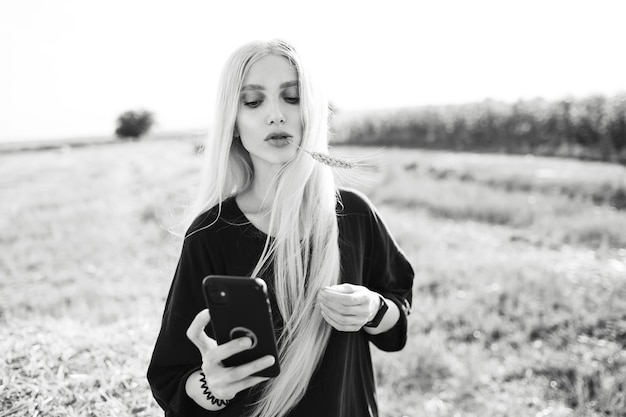Black and white photo of young blonde girl holding a smartphone, in the field.