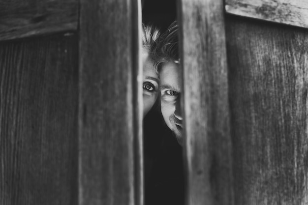 Black and white picture of man and woman hiding in wooden wardrobe