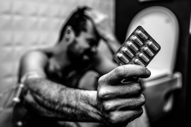 Black and white picture of young man sit on floor in rest room and hold plate of pills. hand is wrapped with plait for taking drugs.