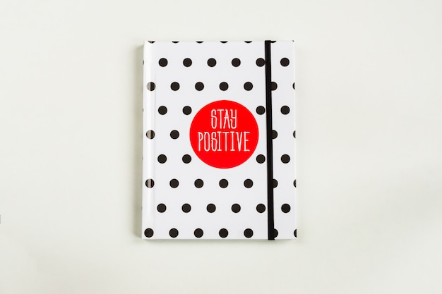 Black and white polka dot note book with red circla and stay positive inscription on the cover.