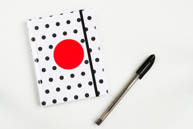 Black and white polka dot note book with red circle  on the cover and black pen on white table. top view, minimal flat lay