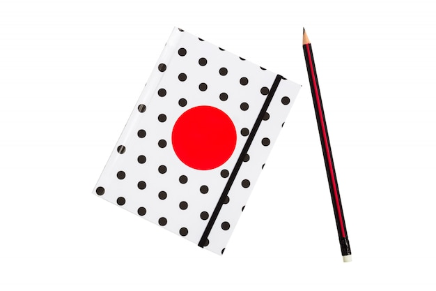 Black and white polka dot note book with red circle  on the cover and black pencil on white background.