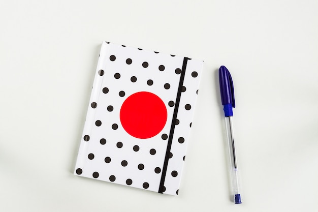 Black and white polka dot note book with red circle  on the cover and blue pen on white table. top view, minimal flat lay