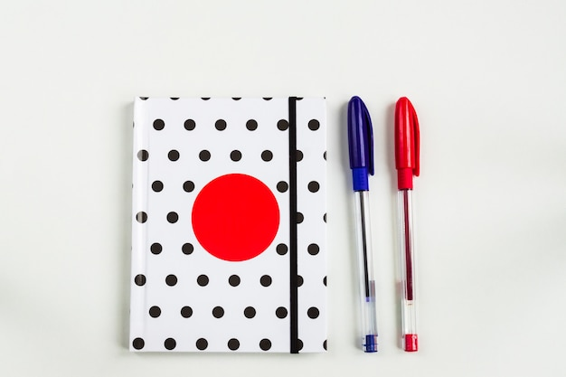 Black and white polka dot note book with red circle  on the cover and blue and red pens on white table. top view, minimal flat lay