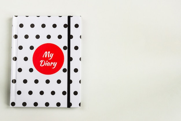 Black and white polka dot note book with red circle and my diary inscription on the cover.