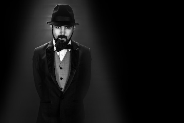 Black and white portrait of bearded smoking gentleman in a suit
