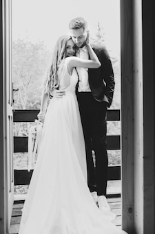 Black and white portrait of a beautiful bride and groom embracing while sitting at the balcony while bride is looking at camera smiling.