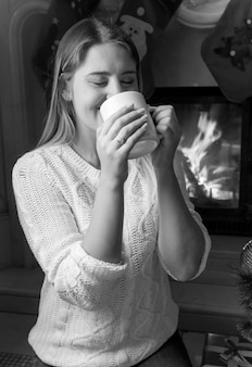 Black and white portrait of beautiful young woman drinking tea at the fireplace