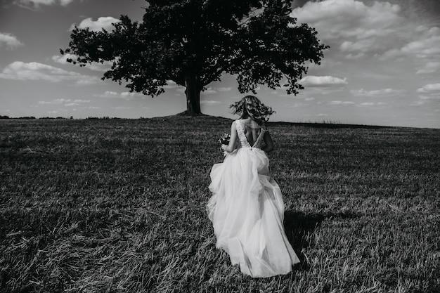 Black-white portrait of a bride running in a field.