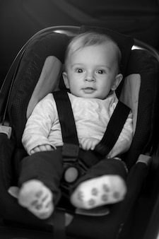 Black and white portrait of cute baby boy sitting in car safety seat