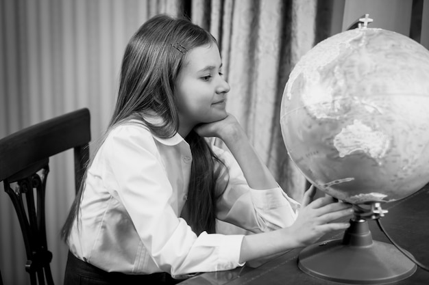 Black and white portrait of cute schoolgirl looking at big globe on table