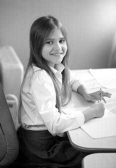 Black and white portrait of cute smiling schoolgirl posing behind desk at bedroom