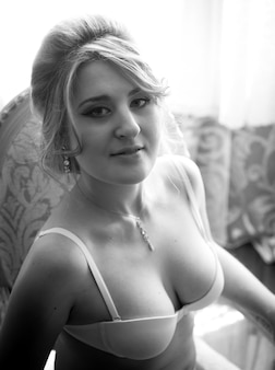 Black and white portrait of elegant woman in bra posing on chair at hotel room