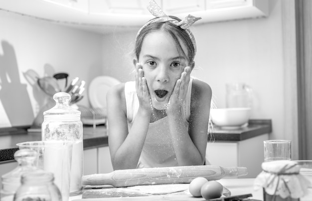 Black and white portrait of excited girl clapping on her cheeks with flour while cooking